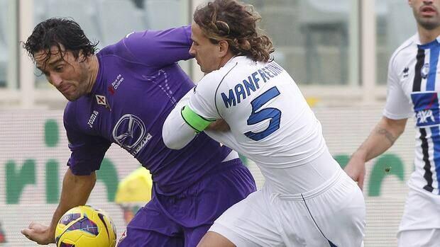 Fiorentina's Luca Toni, left, is challenged by Atalanta's Thomas Manfredini at the Artemio Franchi stadium in Florence, Italy, Sunday, Nov. 18, 2012.