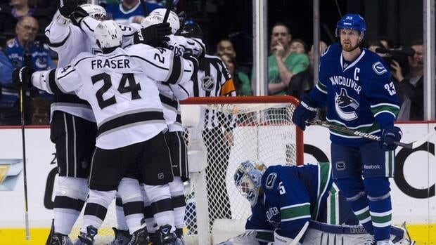 Henrik Sedin of the Vancouver Canucks, right, looks on as Los Angeles Kings players celebrate.