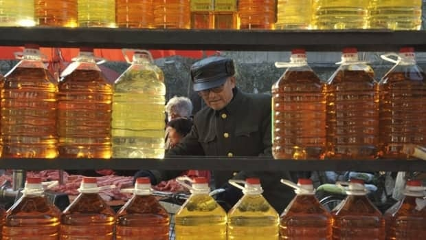 A man looks at cooking oil on sale in a market in Shenyang in northeast China in November 2008. Rising prices of edible cooking oils in recent years have pushed some restaurant owners and drug suppliers to turn to cheaper alternatives, including gutter oil, repurposed cooking oil salvaged from drains and restaurant waste.