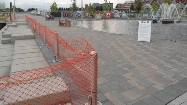 The city of Thunder Bay has temporarily installed snowfencing at the edge of the waterfront splashpad to stop kids from going down into Lake Superior.  Jen Keiller/CBC