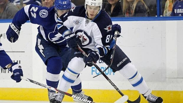The Winnipeg Jets' Alex Burmistrov, right, tries to avoid the check of the Tampa Bay Lightning's Ryan Shannon during a game in Tampa, Florida, on Feb. 2.