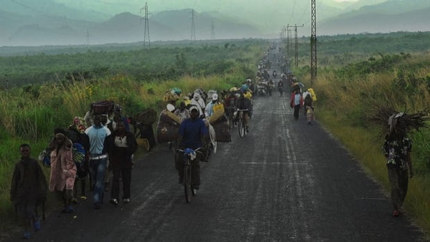 Congolese people carrying their children and belongings flee from Sake on a road linking Goma and Bukavu while escaping on Friday a rebel advance.