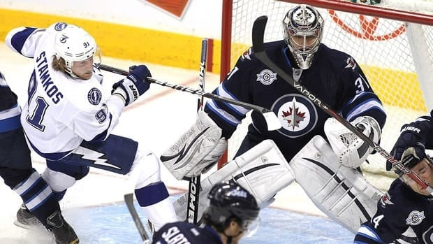 Steven Stamkos of the Tampa Bay Lightning, left, scramble in front of goaltender Ondrej Pavelec of the Winnipeg Jets at the MTS Centre on April 7, 2012 in Winnipeg, Manitoba, Canada.