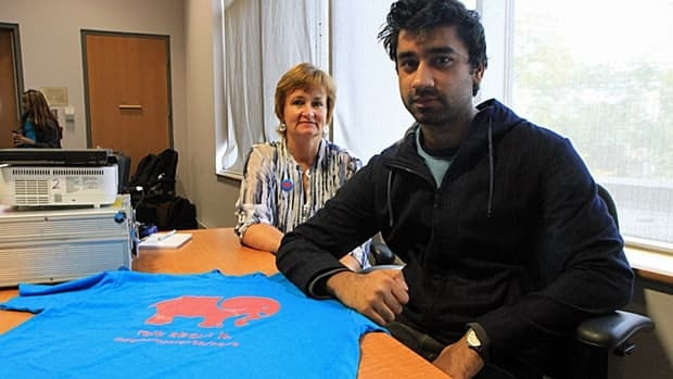 Debra Earl, mental health team nurse, and Huzaifa Saeed, vice-president education with the McMaster Students Union, pose with a T-shirt promoting mental illness awareness week. The pair spoke at a session at McMaster on Monday. (Samantha Craggs/CBC)