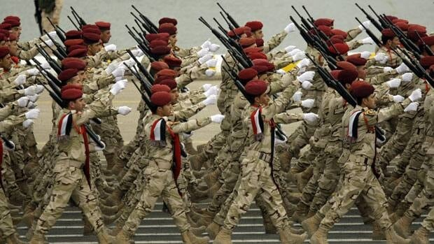 Iraqi Army soldiers march at the Monument of the Unknown Soldier during the Army Day celebrations in Baghdad on Friday. A string of explosions could be heard outside the Green Zone as the parade continued.
