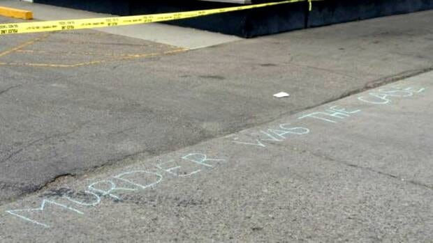 Just a few steps away from this message scrawled in blue chalk is what looks like a large blood stain in the middle of the street.