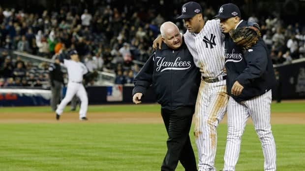 Trainer Steve Donohue, left, and New York Yankees manager Joe Girardi, right, help Derek Jeter off the field after he injured himself during Game 1 of the American League championship series against the Detroit Tigers Sunday.