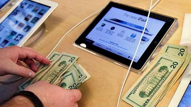 An Apple employee counts money as a customer purchases Apple's new iPad in New York March 16. The company announced Monday it will use some of its vast cash holding to pay a dividend to shareholders.