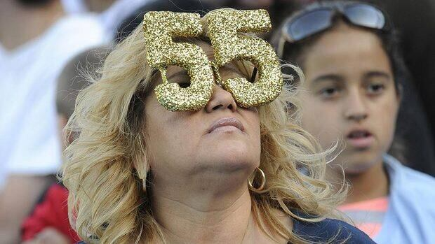 Annette Bush wears sunglasses with Junior Seau's No. 55 before a public memorial for the former NFL star at Qualcomm Stadium in San Diego.