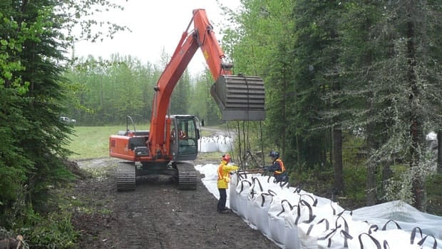 Yukon Wildland Fire Management, Highways and Public Works and hired private contractors are reinforcing decayed portions of an existing sandbag dike on the Liard River and building an additional dike behind the existing one.