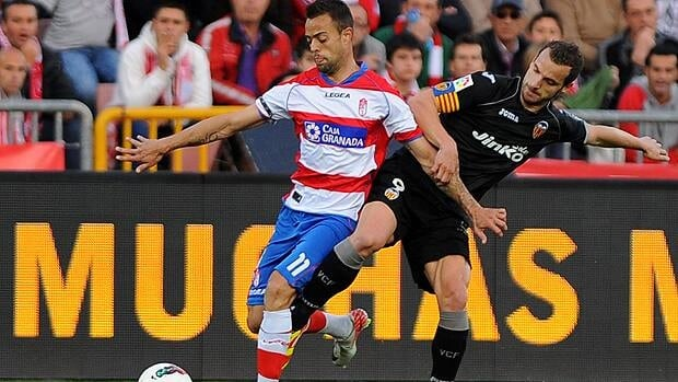Granada's midfielder Dani Benitez (L) vies for the ball with Valencia's forward Roberto Soldado (R) during a Spanish league football match.