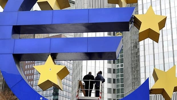 Workers change tube lights of the Euro sculpture in front of the European Central Bank in Frankfurt, Germany on Tuesday.