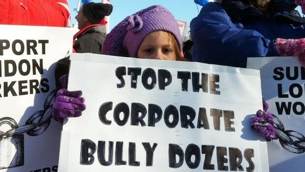 A child holds up a protest sign at a rally to end the three-week lockout of nearly 500 workers at Caterpillar's Electro-Motive plant in London, Ont.