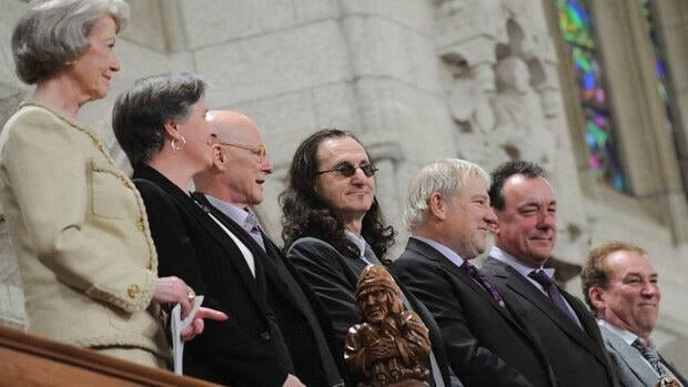Geddy Lee, centre, of Rush, stands with fellow recipients of the 2012 Governor General's Performing Arts Awards as they are acknowledged in the House of Commons on Thursday.