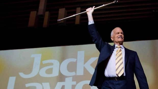 NDP Leader Jack Layton raises his cane during an event in Vancouver on June 19, 2011.
