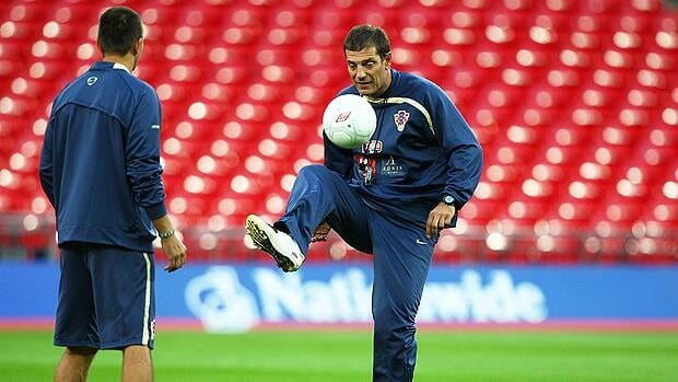 Croatia coach Slaven Bilic plays with a ball while his team warm up for training.