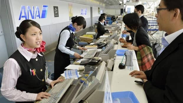 Employees deal with passengers at the counter at Sendai Airport in Sendai, northern Japan, after flights were cancelled Tuesday when an unexploded bomb believed to be from World War II was found during construction near a runway.