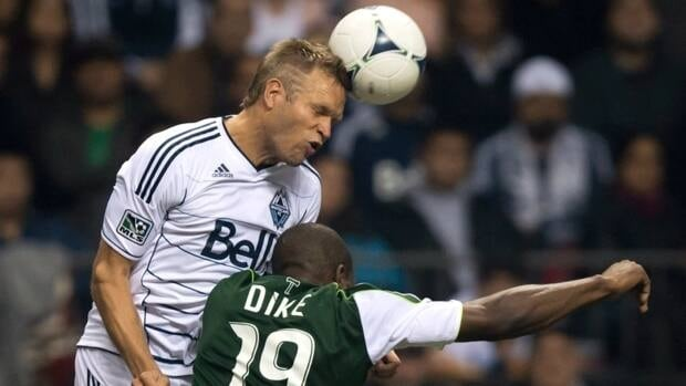 Vancouver Whitecaps' Jay DeMerit, left, heads the ball as Portland Timbers' Bright Dike challenges during the second half of an MLS soccer game in Vancouver, B.C., on Oct. 21.