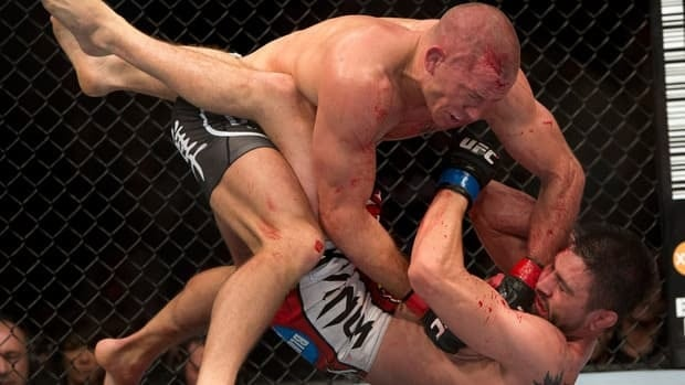Carlos Condit, bottom, battles with Georges St-Pierre during their UFC welterweight title fight Sunday, November 18, 2012 in Montreal.