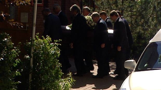 Pallbearers carry Peter Lougheed's coffin into the church on Thursday for a private funeral.