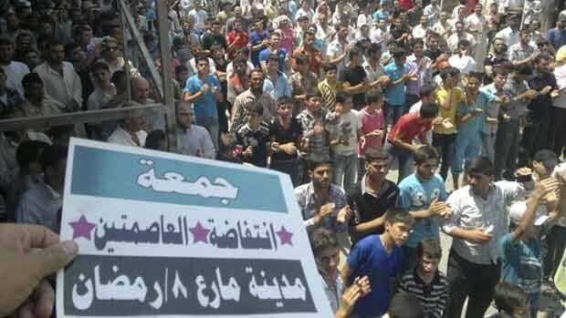 Demonstrators protest against Syria's President Bashar al-Assad after Friday prayers in Maraa, near Aleppo, July 27. The placard reads: Friday of the two capitals uprising.