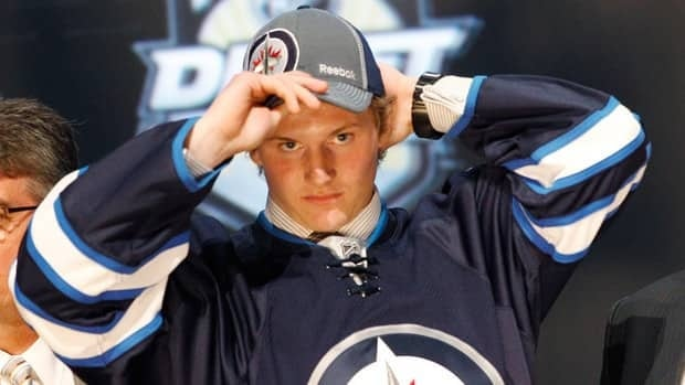 Defenceman Jacob Trouba, centre, pulls on a Winnipeg Jets cap after being chosen ninth overall in the first round on Friday.