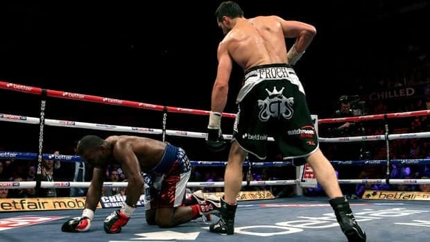 Britain's Carl Froch, right, stands above American Yusaf Mack in the third round of their bout in Nottingham on Saturday.