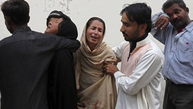 Family members of Nasima Bibi, a female worker of an anti-polio drive campaign who was shot by gunmen, mourn at a hospital morgue in Karachi on Tuesday.