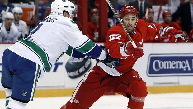 Red Wings defenceman Kyle Quincey, in his first game since being re-acquired by Detroit this week, is checked by Canucks defenceman Dan Hamhuis, left, in the first period.