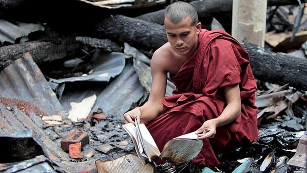 A Bangladeshi Buddhist monk checks the remains of burned religious books at a Buddhist temple which was torched in an overnight weekend attack in Ramu in the coastal district of Cox's Bazar, Bangladesh, Monday.