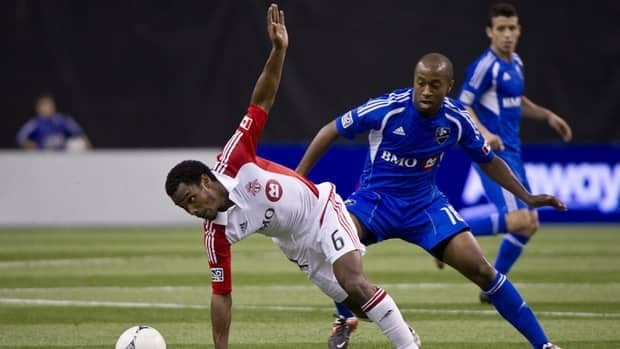 Toronto FC's Julian de Guzman slips as he goes for the ball ahead of Montreal Impact's Collen Warner during the second half on Wednesday.
