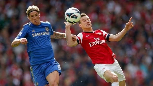 Arsenal's Laurent Koscielny, right, competes for the ball with Chelsea's Fernando Torres in Saturday's action. Chelsea stayed at the top of the table with a victory.
