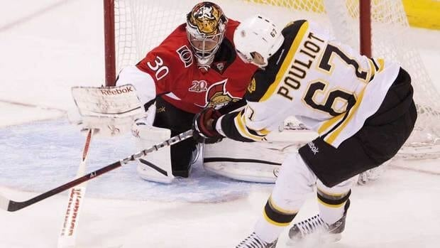 Ottawa Senators goalie Ben Bishop poke checks the puck away from Boston Bruins left wing Benoit Pouliot infront of the net during the first period of Thursday night's game in Ottawa.