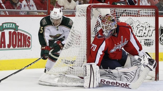 Washington Capitals goalie Braden Holtby guards the post during the second period as Minnesota's Nick Johnson skates behind the net.
