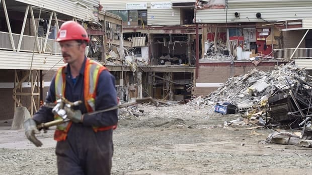 A worker walks back from rubble at the Algo Centre Mall in Elliot Lake, Ont., in late June. Ottawa Justice Paul Belanger will lead the independent inquiry into the June 23 collapse