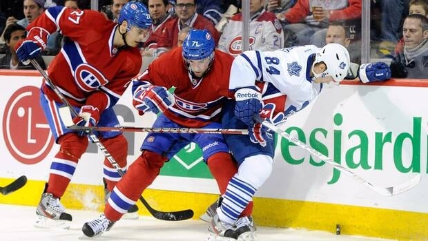 Montreal's Louis Leblanc, centre, battles for the puck with Toronto's Mikhail Grabovski, right, who burned the Habs for two goals on Saturday night.