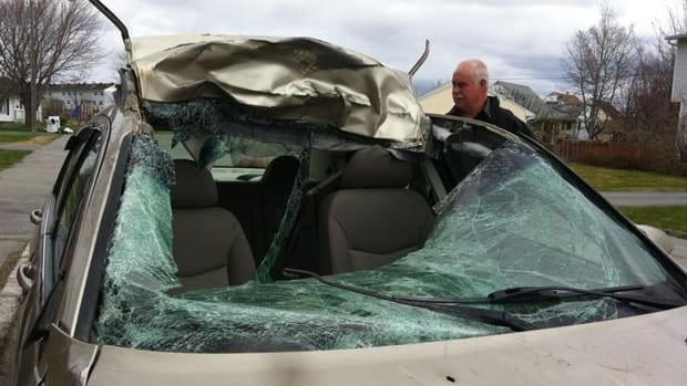 Michelle Higgins, of Norris Arm, doesn't remember driving about 40 kilometres in this car after hitting a moose. She has since visited the site of the crash with her father, seen standing beside the car here.