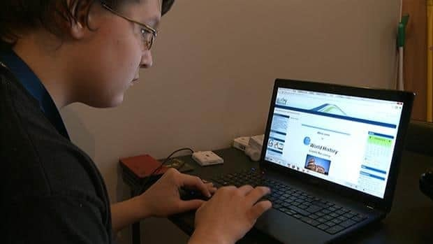 Brett Klein, 15, studies online from his kitchen.