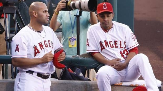 Albert Pujols , left, sitting out Saturday's game and sharing a chat with Maicer Izturis. It was the first time the $240-million man has sat out this season and was done in hopes of refocussing the slugger.