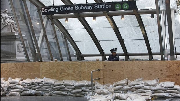 A police officer guards the entrance to a N.Y. subway station. Hurricane Sandy has effectively shut down the entire city.