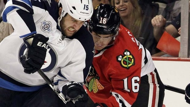 Winnipeg Jets' Tanner Glass, left, battles for the puck with Chicago Blackhawks' Marcus Kruger (16).