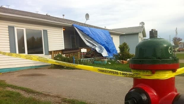 Police tape cordons off a home on Saskatoon Drive in Hay River, N.W.T., where police found an injured woman Monday night. She later died in hospital.