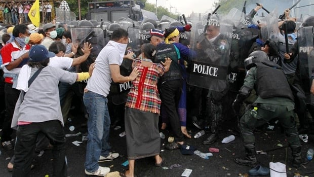 Police scuffle with anti-government protesters near the government house in Bangkok .