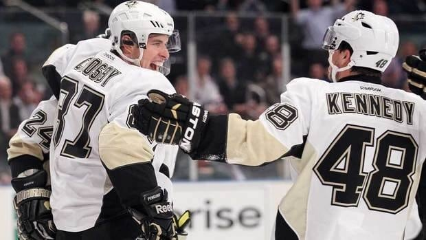 Penguins captain Sidney Crosby (87) celebrates a first-period goal by Matt Cooke (24), along with linemate Tyler Kennedy (48).