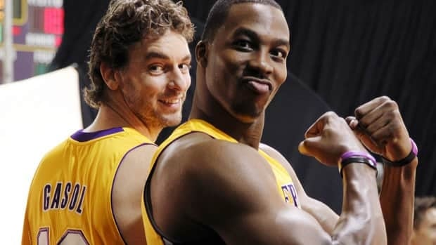 Lakers centre Dwight Howard flexes his biceps as Pau Gasol looks on during the team's NBA media day on Monday.