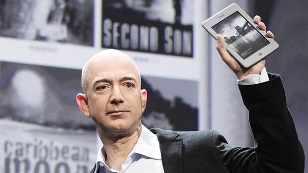 Amazon.com CEO Jeff Bezos shows off a Kindle in New York in September. Penguin cited 'concerns about the security of our digital editions' for its decision to suspend new e-book titles for libraries and to disallow library loans of e-books for the Kindle.