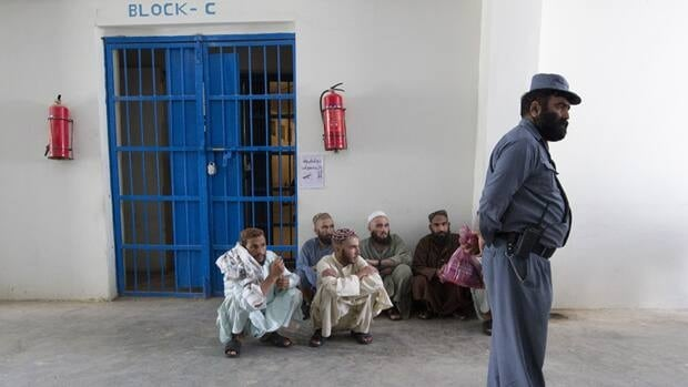 An Afghan policeman stands in front of inmates in a prison in the town of Lashkar Gah in Helmand province, southern Afghanistan, July 19, 2011.