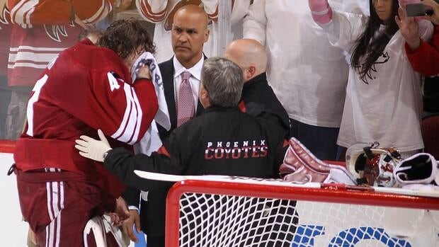 Coyotes goaltender Mike Smith, left, is attended to by the team doctor after a hard collision with Chicago forward Andrew Shaw, not pictured, on Saturday.