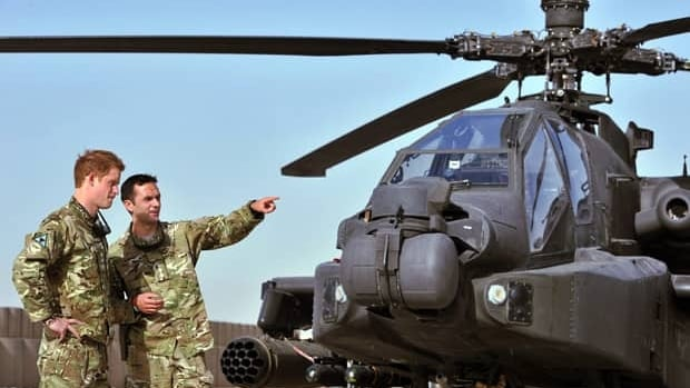 Prince Harry is shown the Apache flight-line on Friday by a member of his squadron at Camp Bastion in Afghanistan.