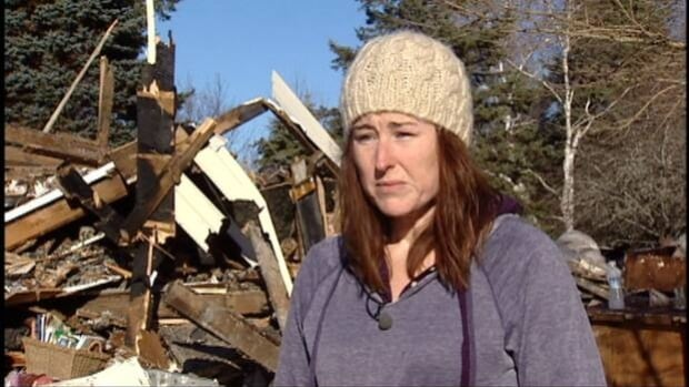 Amanda Heitkemper stands in front of her leveled home. She says she's already planning to help the next family in need.